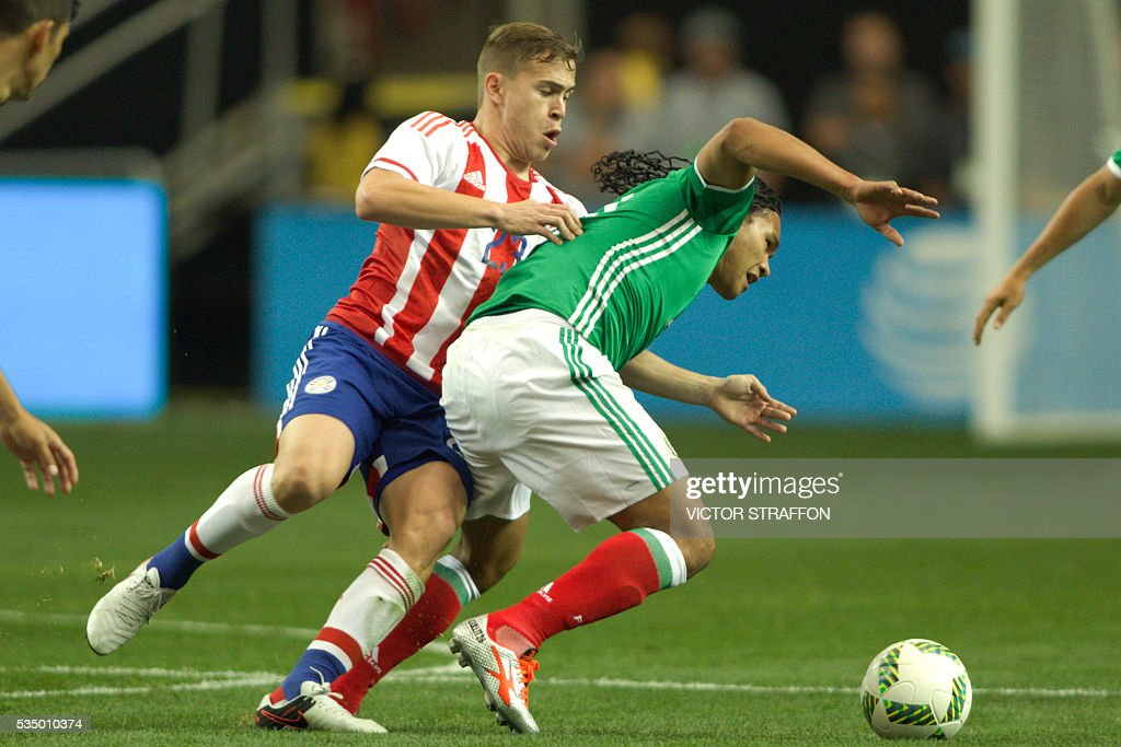 Carlos Pena of Mexico (R) vies for the ball with Robert AndresPiris (L) of Paraguay during the friendly match between the Mexican national team and Paraguay national team at the Georgia Dome in Atlanta, Georgia on May 28, 2016. / AFP / VICTOR