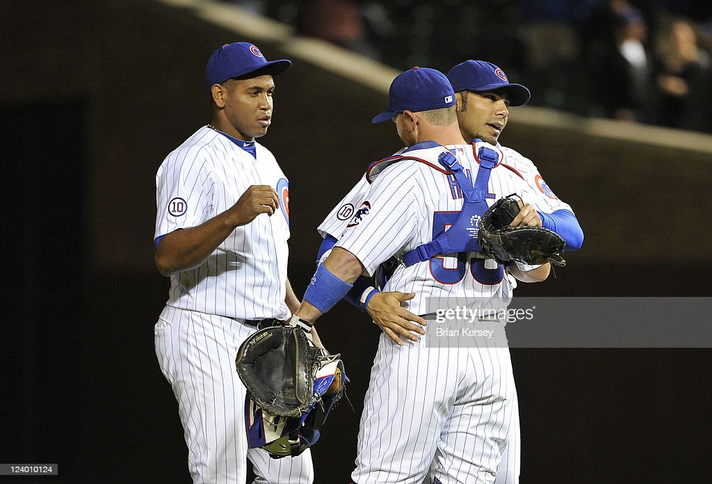 Carlos Pena #22 (C) of the Chicago Cubs hugs teammate <a gi-track='captionPersonalityLinkClicked' href=/galleries/search?phrase=Koyie+Hill&family=editorial&specificpeople=221625 ng-click='$event.stopPropagation()'>Koyie Hill</a> #55 (R) as they celebrate their 6-3 win over the Cincinnati Reds with teammate <a gi-track='captionPersonalityLinkClicked' href=/galleries/search?phrase=Carlos+Marmol&family=editorial&specificpeople=556707 ng-click='$event.stopPropagation()'>Carlos Marmol</a> #49 at Wrigley Field on September 7, 2011 in Chicago, Illinois.
