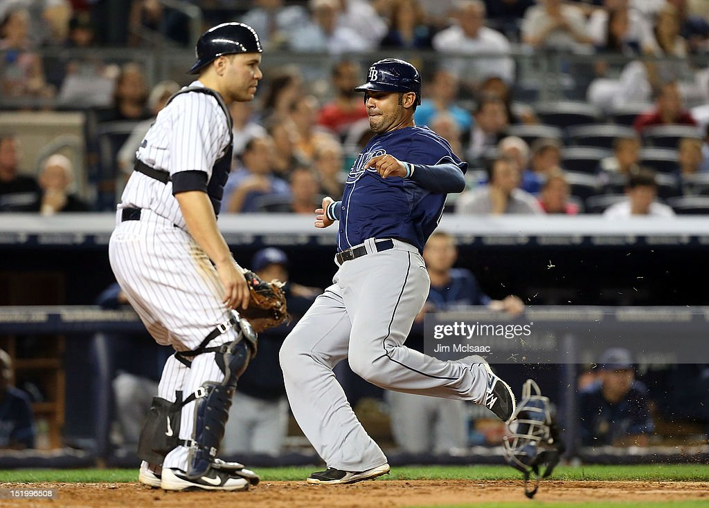 Carlos Pena #23 of the Tampa Bay Rays scores a fifth inning run past <a gi-track='captionPersonalityLinkClicked' href=/galleries/search?phrase=Russell+Martin+-+Baseball+Player&family=editorial&specificpeople=13764024 ng-click='$event.stopPropagation()'>Russell Martin</a> #55 of the New York Yankees at Yankee Stadium on September 14, 2012 in the Bronx borough of New York City.