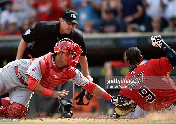 Carlos Perez of the Los Angeles Angels of Anaheim defends home plate against Eduardo Nunez of the Minnesota Twins during the seventh inning of the...