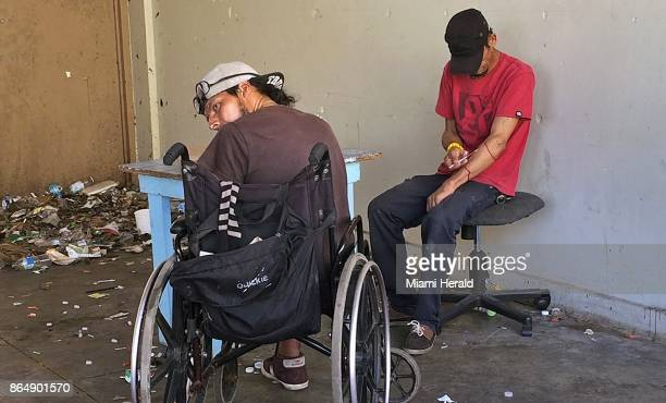 Carlos Perrios right injects himself with drugs as Oliver Franco Rivero looks over his shoulder while sitting in a shooting den at an abandoned...