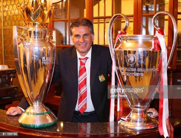 Carlos Queiroz of Manchester United poses with the UEFA Champions League trophy and the FA Barclays Premier League trophy after winning the UEFA...