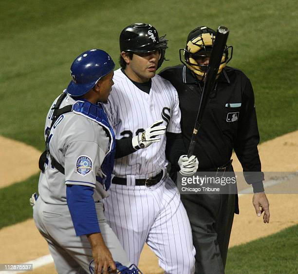Carlos Quentin of the Chicago White Sox center is restrained by catcher Miguel Olivo of the Kansas City Royals and umpire Bill Hohn after being hit...
