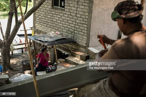 Carlos Ramirez works on metal sheeting for a rain gutter on July 16 2015 in La Lapara Mexico This area is a base of operations for El Chapo's Sinaloa...