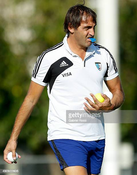 Carlos Retegui coach of Las Leonas and Los Leones holds balls on his hands while walking on the field during a training session as part of Argentina...