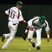 Carlos Riberos and Oscar Robles of Yaquis of Mexico reach for the ball during their Caribbean Series game against Aguilas del Cibao of the Dominican...