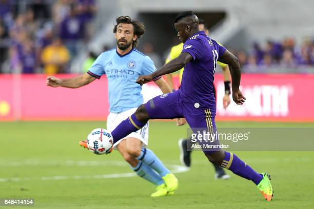 Carlos Rivas of Orlando City SC kicks the ball past Andrea Pirlo of New York City FC during a MLS soccer match between New York City FC and Orlando...