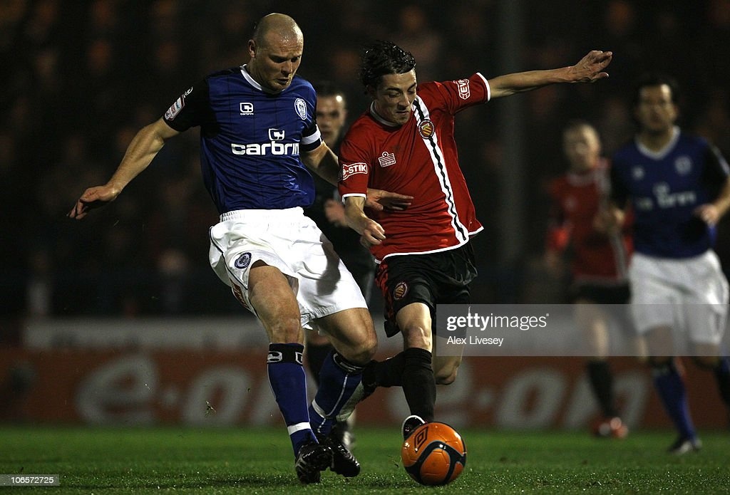 Carlos Roca of FC United of Manchester beats Gary Jones of Rochdale during the FA Cup 1st Round match sponsored by eon at Spotland Stadium on...