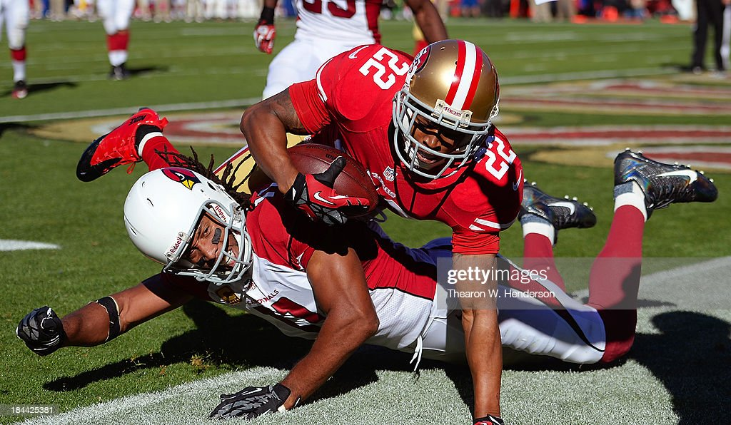 Carlos Rogers #22 of the San Francisco 49ers intercepts a two point conversion try and falls over receiver <a gi-track='captionPersonalityLinkClicked' href=/galleries/search?phrase=Larry+Fitzgerald&family=editorial&specificpeople=183380 ng-click='$event.stopPropagation()'>Larry Fitzgerald</a> #11 of the Arizona Cardinals in the back of the endzone during the third quarter at Candlestick Park on October 13, 2013 in San Francisco, California.