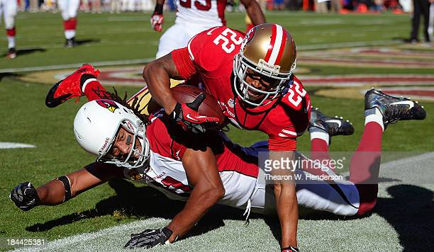 Carlos Rogers of the San Francisco 49ers intercepts a two point conversion try and falls over receiver Larry Fitzgerald of the Arizona Cardinals in...