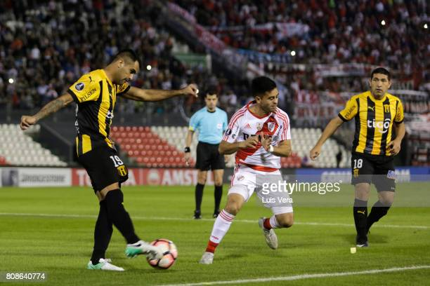 Carlos Rolon of Gurani shoots as Gonzalo Martinez of River Plate tries to block during a first leg match between Guarani and River Plate as part of...