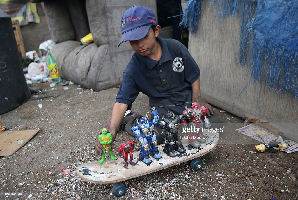 Carlos Roman, 9, plays with toys found at the Tirabichi garbage dump on March 5, 2013 in Nogales, Mexico. About 30 families live at the landfill, searching for recyclables to sell for a living. Many have received protective gloves from the nearby non-profit Home of Hope and Peace, which plans to expand its assistance to Tirabichi residents.