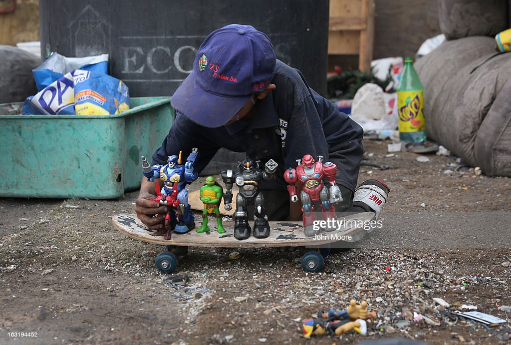 Carlos Roman, 9, plays with toys found while he and family members were working at the Tirabichi garbage dump on March 5, 2013 in Nogales, Mexico. About 30 families, including Carlos, live at the landfill, searching for recyclables to sell for a living. Some residents there were undomumented immigrants who were caught and deported by the United States back to Mexico. They have received aid from the non-profit Home of Hope and Peace, which plans to expand it's assistance to the dump's impoverished populace in the future.
