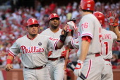 Carlos Ruiz and Ben Francisco of the Philadelphia Phillies celebrate with Chase Utley and Jimmy Rollins after Francisco's threerun home run as Yadier...