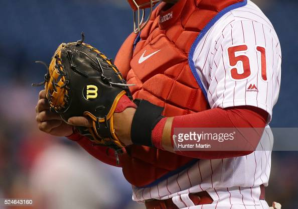 Carlos Ruiz of the Philadelphia Phillies adjusts his Wilson catcher's mitt during a game against the New York Mets at Citizens Bank Park on April 20...
