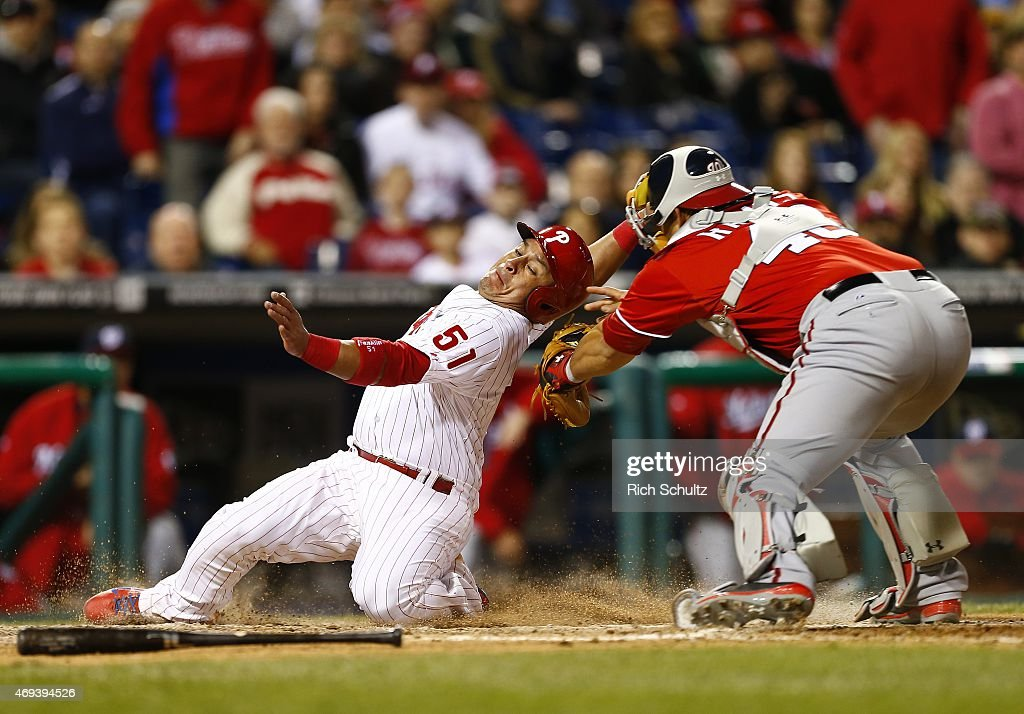 Carlos Ruiz of the Philadelphia Phillies attempts to avoid the tag by catcher Wilson Ramos of the Washington Nationals while trying to score on a...