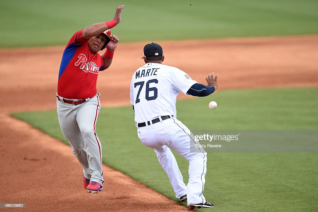 Carlos Ruiz of the Philadelphia Phillies avoids a tag by Jefry Marte of the Detroit Tigers during the first inning of a spring training game at Joker...