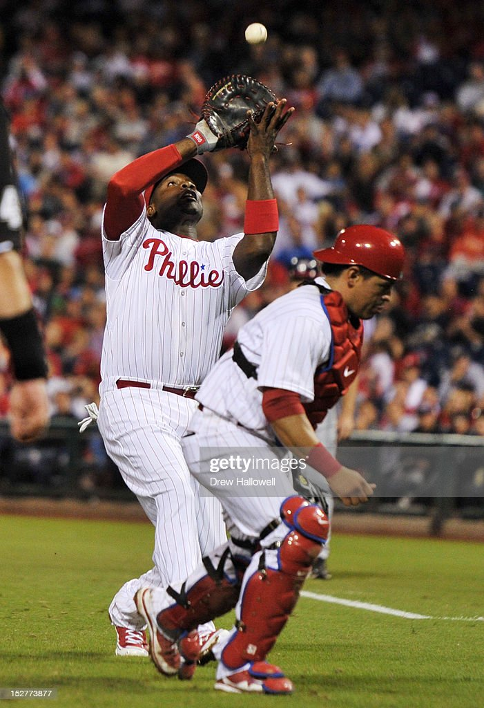 Carlos Ruiz #51 of the Philadelphia Phillies ducks out of the way as <a gi-track='captionPersonalityLinkClicked' href=/galleries/search?phrase=Ryan+Howard&family=editorial&specificpeople=551402 ng-click='$event.stopPropagation()'>Ryan Howard</a> #6 catches a foul ball at Citizens Bank Park on September 25, 2012 in Philadelphia, Pennsylvania. The Phillies won 6-3.