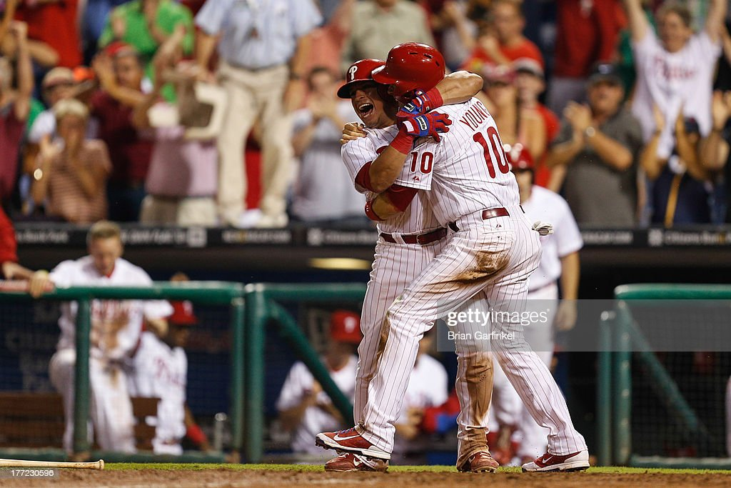 Carlos Ruiz #51 of the Philadelphia Phillies embraces Michael Young #10 after Young scored the game winning run in the bottom of the ninth inning of the game against the Colorado Rockies at Citizens Bank Park on August 22, 2013 in Philadelphia, Pennsylvania. The Phillies won 5-4.