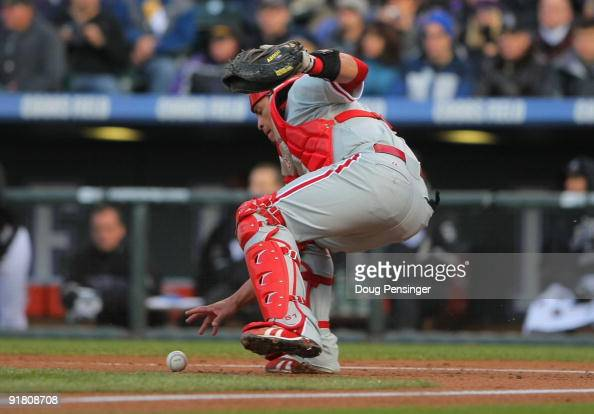Carlos Ruiz of the Philadelphia Phillies fields a wild pitch in the bottom of the first inning against the Colorado Rockies in Game Four of the NLDS...