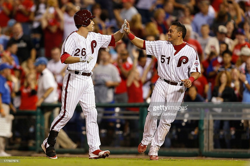 Carlos Ruiz #51 of the Philadelphia Phillies high fives <a gi-track='captionPersonalityLinkClicked' href=/galleries/search?phrase=Chase+Utley&family=editorial&specificpeople=161391 ng-click='$event.stopPropagation()'>Chase Utley</a> #26 after Utley was walked for a walk off walk in the bottom of the ninth inning of the game against the Arizona Diamondbacks at Citizens Bank Park on August 23, 2013 in Philadelphia, Pennsylvania. The Phillies won 4-3.