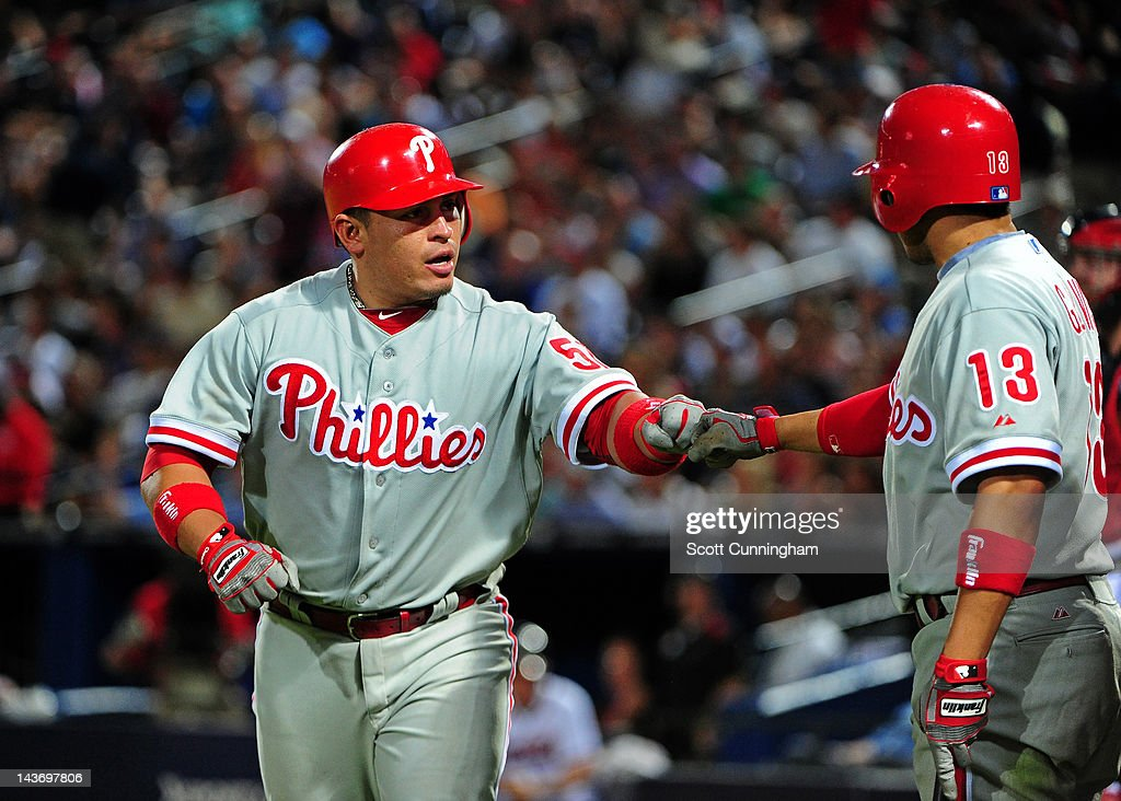 Carlos Ruiz #51 of the Philadelphia Phillies is congratulated by Freddy Galvis #13 after hitting a seventh inning home run against the Atlanta Braves at Turner Field on May 2, 2012 in Atlanta, Georgia.