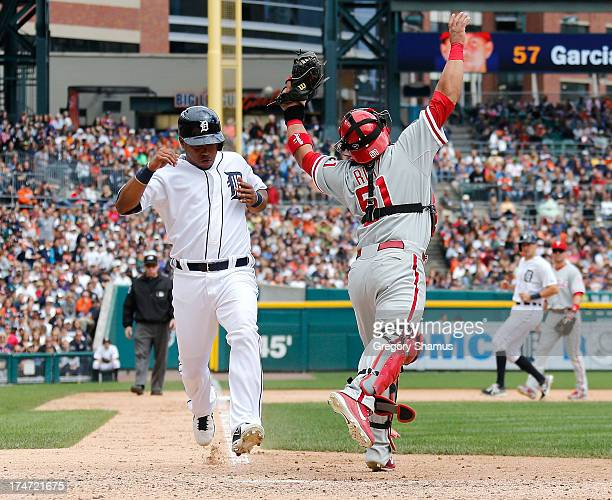 Carlos Ruiz of the Philadelphia Phillies is pulled off the plate on a force out play by a bad throw in the sixth inning next to Ramon Santiago of the...