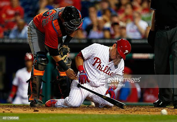 Carlos Ruiz of the Philadelphia Phillies reacts after being hit in the head by a pitch in the 11th inning as catcher Jarrod Saltalamacchia of the...