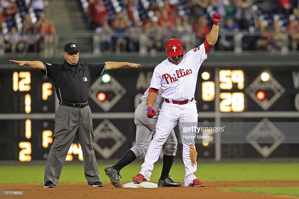 Carlos Ruiz #51 of the Philadelphia Phillies reacts after hitting an RBI double in the ninth inning that tied the score during a game against the Colorado Rockies at Citizens Bank Park on August 21, 2013 in Philadelphia, Pennsylvania. The Phillies won 4-3.