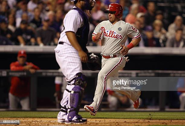 Carlos Ruiz of the Philadelphia Phillies scores behind catcher Wilin Rosario of the Colorado Rockies on a pinch hit RBI single by Jayson Nix of the...