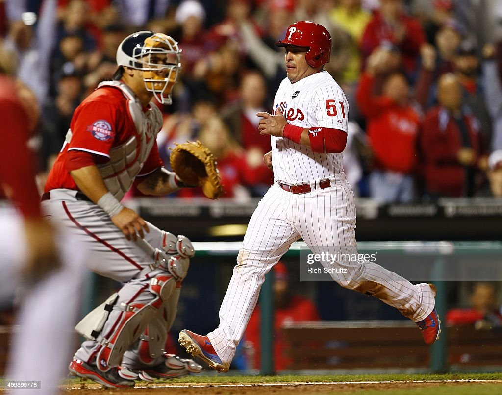 Carlos Ruiz of the Philadelphia Phillies scores the winning run as he passes catcher Wilson Ramos of the Washington Nationals on an Odubel Herrera...