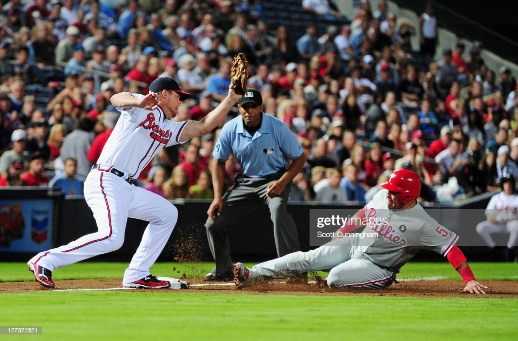 Carlos Ruiz #51 of the Philadelphia Phillies slides safely in to third base against <a gi-track='captionPersonalityLinkClicked' href=/galleries/search?phrase=Chipper+Jones&family=editorial&specificpeople=171256 ng-click='$event.stopPropagation()'>Chipper Jones</a> #10 of the Atlanta Braves at Turner Field on September 27, 2011 in Atlanta, Georgia.