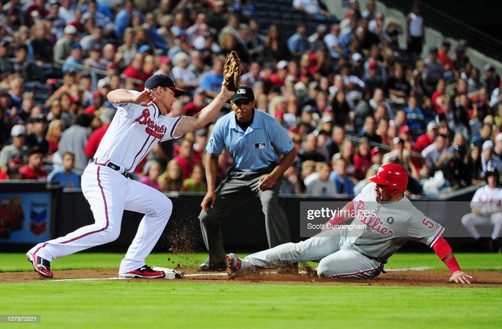 Carlos Ruiz of the Philadelphia Phillies slides safely in to third base against Chipper Jones of the Atlanta Braves at Turner Field on September 27...