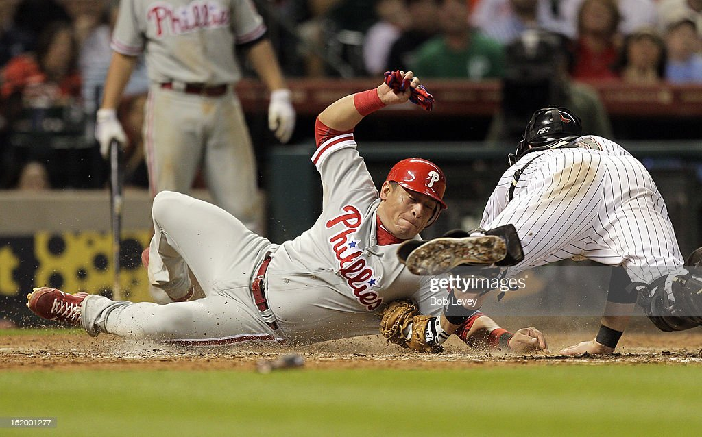 Carlos Ruiz #51 of the Philadelphia Phillies slides safely into home as catcher <a gi-track='captionPersonalityLinkClicked' href=/galleries/search?phrase=Chris+Snyder&family=editorial&specificpeople=201238 ng-click='$event.stopPropagation()'>Chris Snyder</a> #18 of the Houston Astros is late on the tag in the fifth inning at Minute Maid Park on September 14, 2012 in Houston, Texas.