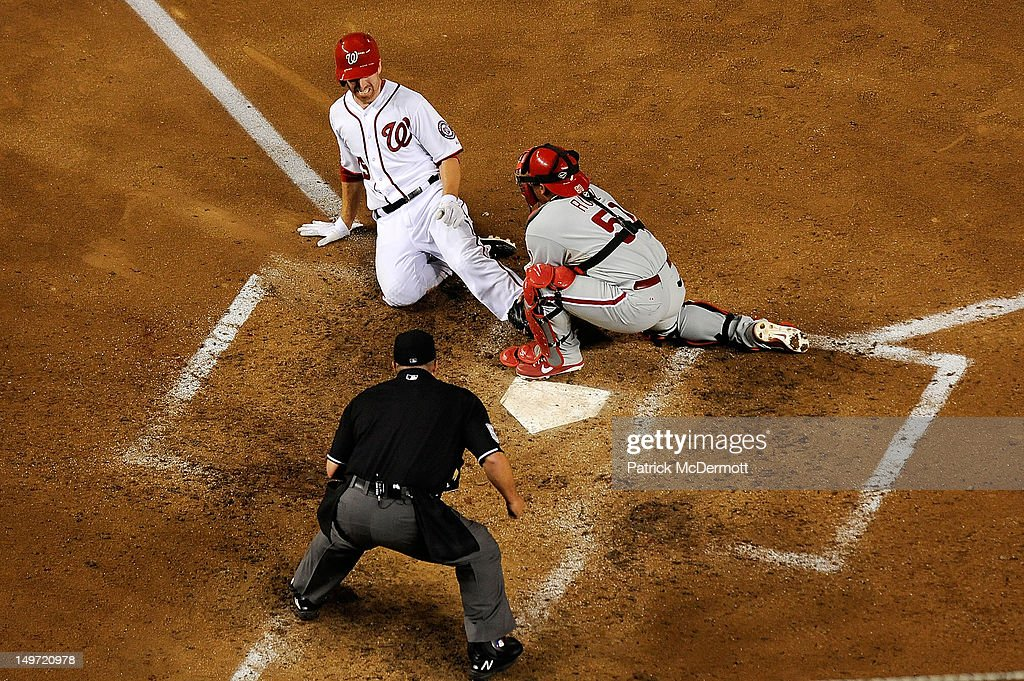 Carlos Ruiz of the Philadelphia Phillies tags Adam LaRoche of the Washington Nationals out at home plate in the sixth inning during a game at...