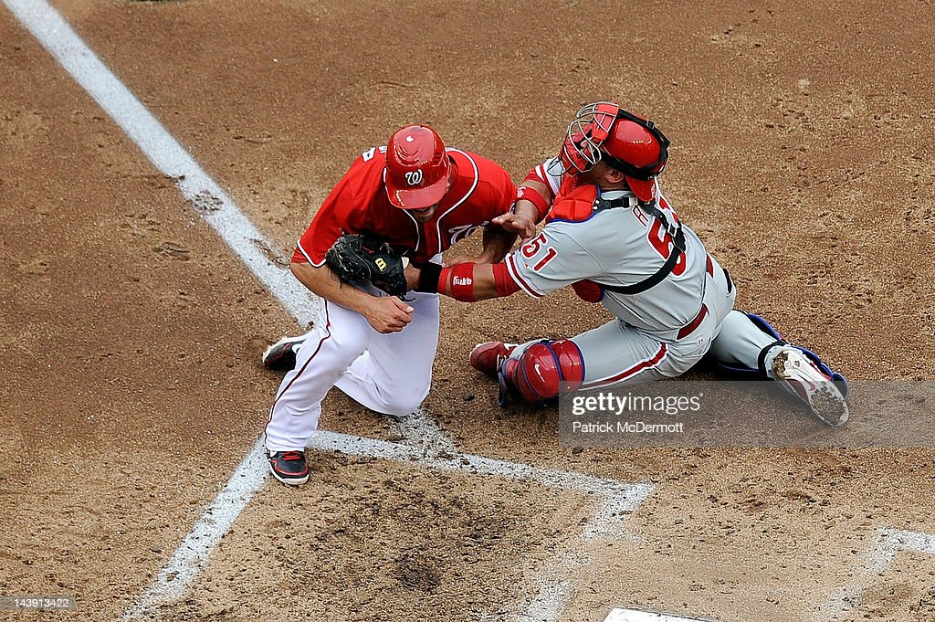 Carlos Ruiz of the Philadelphia Phillies tags Danny Espinosa of the Washington Nationals out at home plate in the fifth inning at Nationals Park on...