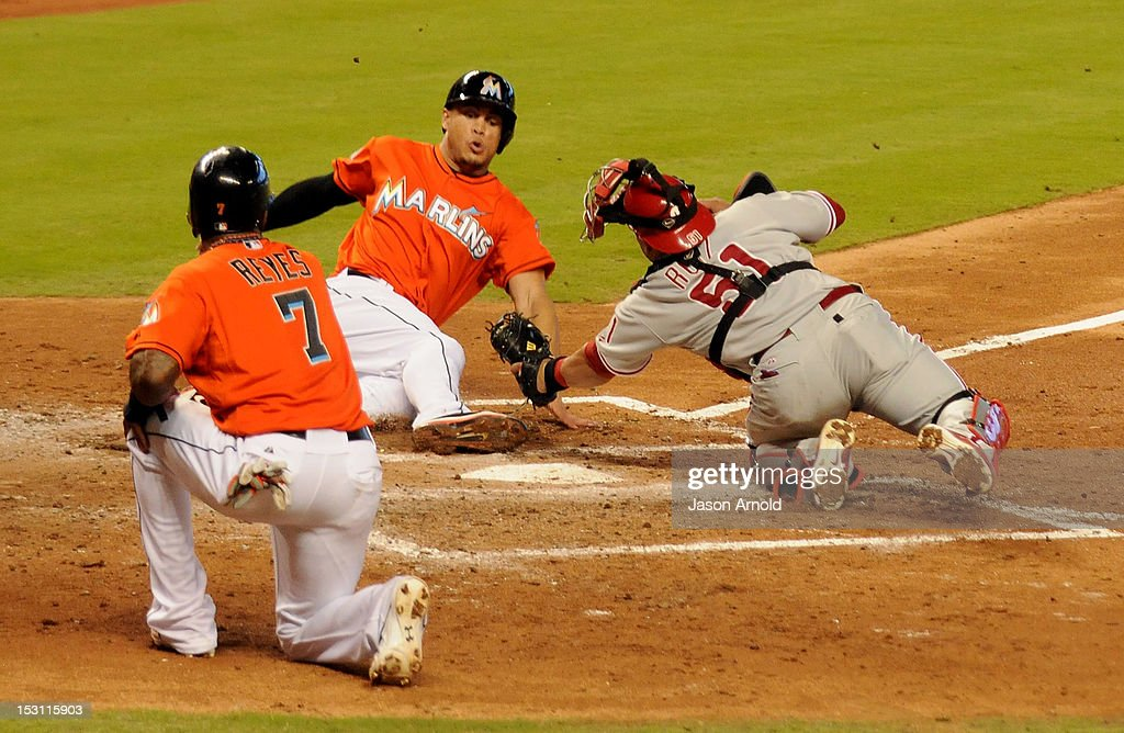 Carlos Ruiz #51 (R) of the Philadelphia Phillies tags out <a gi-track='captionPersonalityLinkClicked' href=/galleries/search?phrase=Giancarlo+Stanton&family=editorial&specificpeople=8983978 ng-click='$event.stopPropagation()'>Giancarlo Stanton</a> #27 (C) of the Miami Marlins as Jose Reyes #7 (L) watches at Marlins Park on September 30, 2012 in Miami, Florida.
