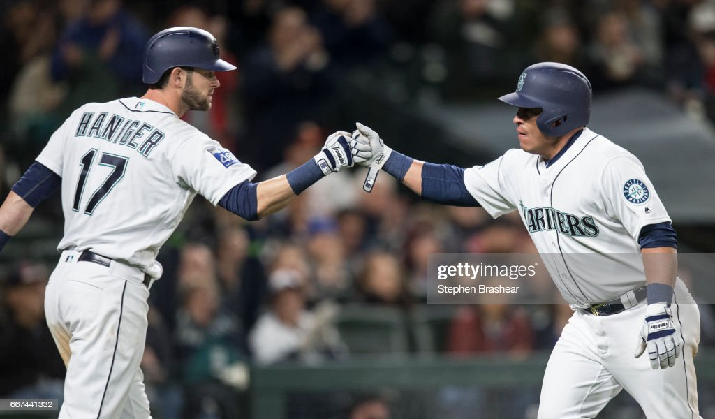 Carlos Ruiz #52, right, of the Seattle Mariners is congratulated by teammate Mitch Haniger #17 of the Seattle Mariners after Ruiz scored sacrifice fly by Jarrod Dyson #1 of the Seattle Mariners off of starting pitcher Joe Musgrove #59 of the Houston Astros during the fifth inning of a game at Safeco Field on April 11, 2017 in Seattle, Washington.
