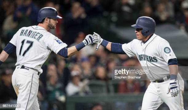 Carlos Ruiz right of the Seattle Mariners is congratulated by teammate Mitch Haniger of the Seattle Mariners after Ruiz scored sacrifice fly by...