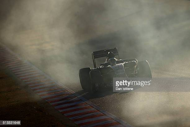 Carlos Sainz of Spain and Scuderia Toro Rosso drives through smoke from the wheels of Pascal Wehrlein of Germany and Manor's tyres during day two of...
