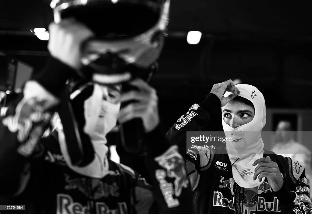 Carlos Sainz of Spain and Scuderia Toro Rosso prepares next to teammate Max Verstappen of Netherlands and Scuderia Toro Rosso in the garage during...
