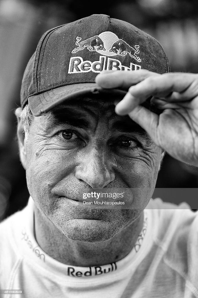 Carlos Sainz of Spain for the SMG Buggy and Red Bull Rally Team sits in front of his car as mechanics work on it during Day 4 of the 2014 Dakar Rally on January 8, 2014 in Chilecito, Argentina.