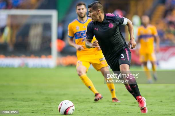 Carlos Salcido of Chivas drives the ball while observed by Andre Gignac of Tigres during the 12th round match between Tigres UANL and Chivas as part...