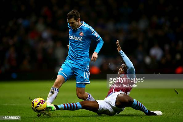 Carlos Sanchez of Aston Villa slides in on Adam Johnson of Sunderland during the Barclays Premier League match between Aston Villa and Sunderland at...