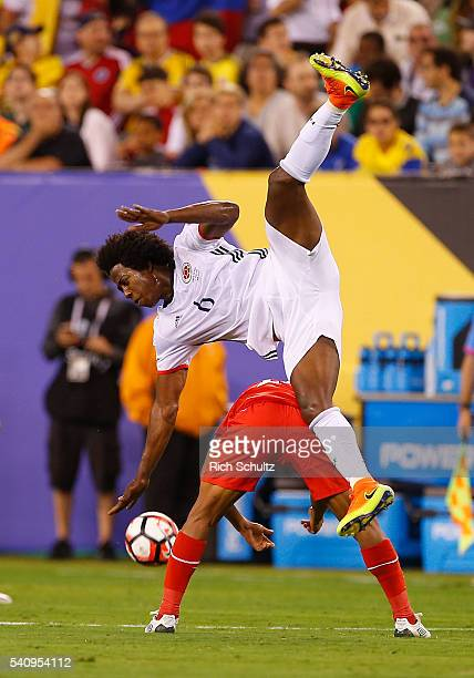 Carlos Sanchez of Colombia falls over Edison Flores of Peru after going for a header during a Quarterfinal match at MetLife Stadium as part of Copa...