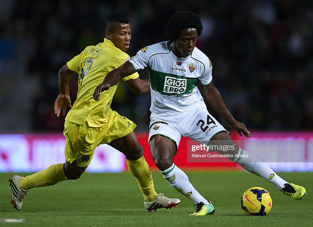 Carlos Sanchez (R) of Elche competes for the ball with <a gi-track='captionPersonalityLinkClicked' href=/galleries/search?phrase=Ikechukwu+Uche&family=editorial&specificpeople=4852786 ng-click='$event.stopPropagation()'>Ikechukwu Uche</a> of Villarreal during the La Liga match between Elche CF and Villarreal CF at Estadio Manuel Martinez Valero on November 4, 2013 in Elche, Spain.