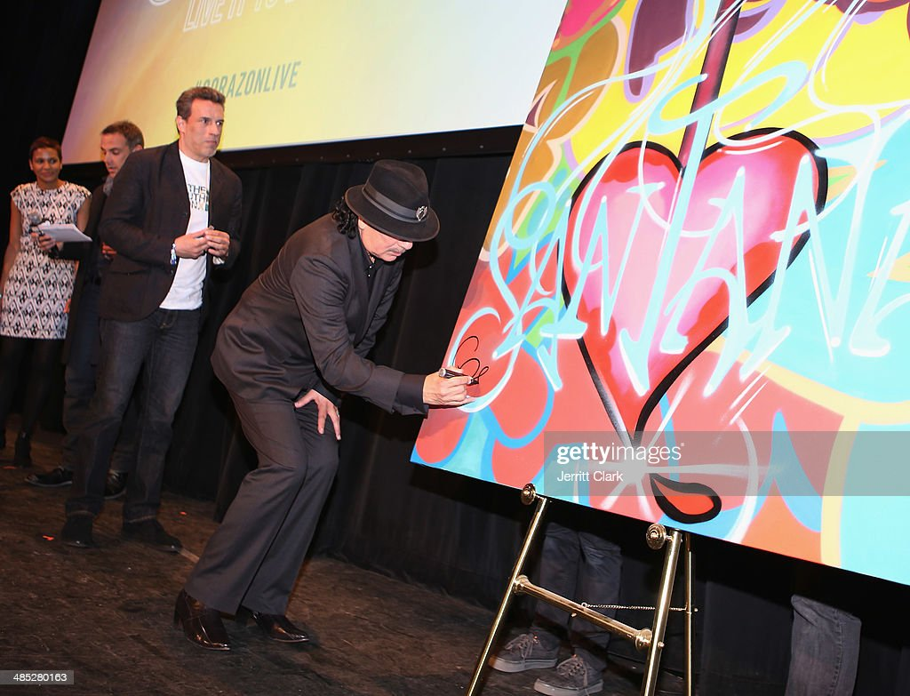 Carlos Santana and muralist John 'Crash' Matos sign artwork created by Crash to be sold at auction benefitting Milagro Foundation during the HBO Latino NYC Premiere of 'Santana: De Corazon' at Hudson Theatre on April 16, 2014 in New York City.