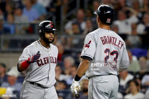 Carlos Santana of the Cleveland Indians celebrates with Michael Brantley after hitting a two run home run scoring Jay Bruce against Luis Severino of...