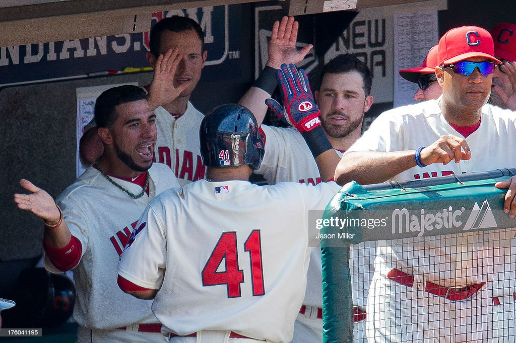 Carlos Santana #41 of the Cleveland Indians celebrates with teammates after hitting a solo home run during the seventh inning against the Los Angeles Angels of Anaheim to tie the game at Progressive Field on August 11, 2013 in Cleveland, Ohio.