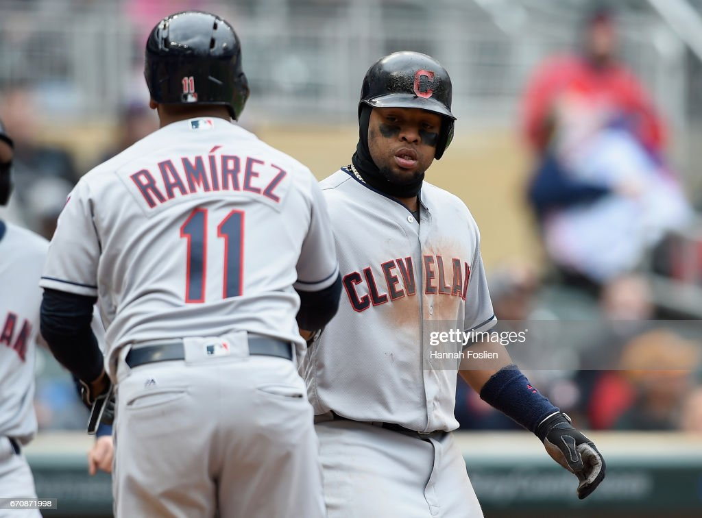 Carlos Santana #41 of the Cleveland Indians congratulates teammate Jose Ramirez #11 on drawing a bases loaded walk against the Minnesota Twins that scored Santana in the seventh inning on April 20, 2017 at Target Field in Minneapolis, Minnesota. The Indians defeated the Twins 6-2.